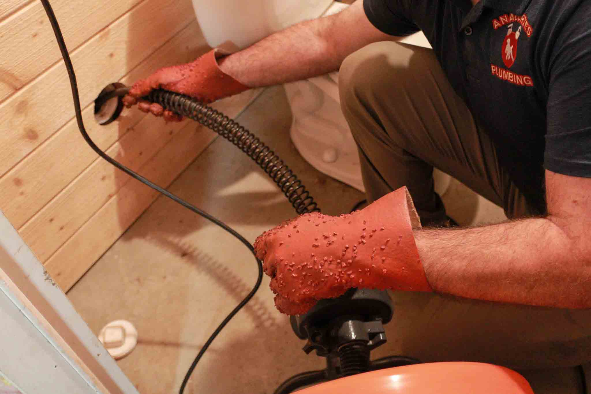 Anacortes Plumbing plumber cleaning a clogged drain.