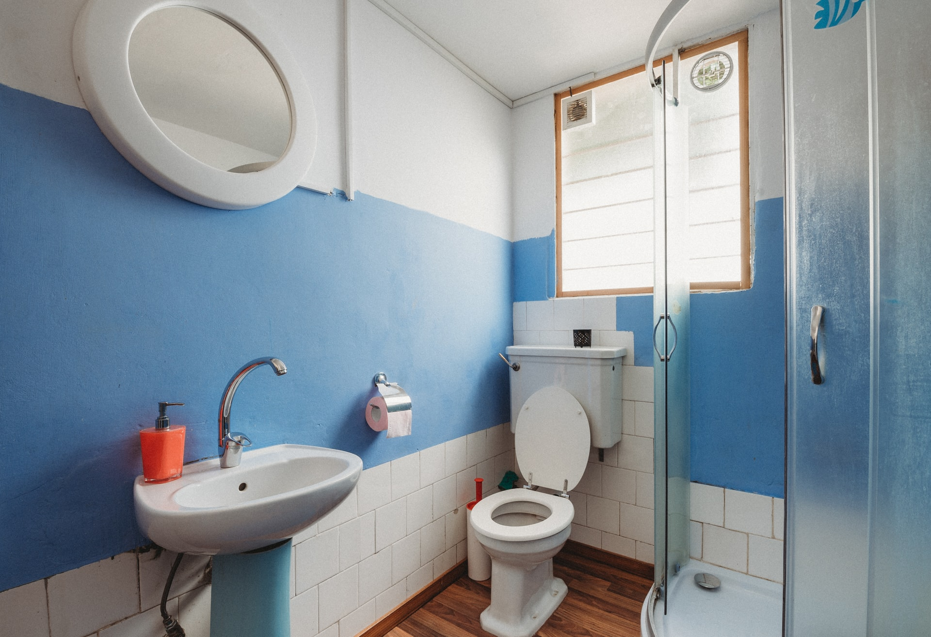 bathroom with a toilet, sink, tub, and a leaky faucet.