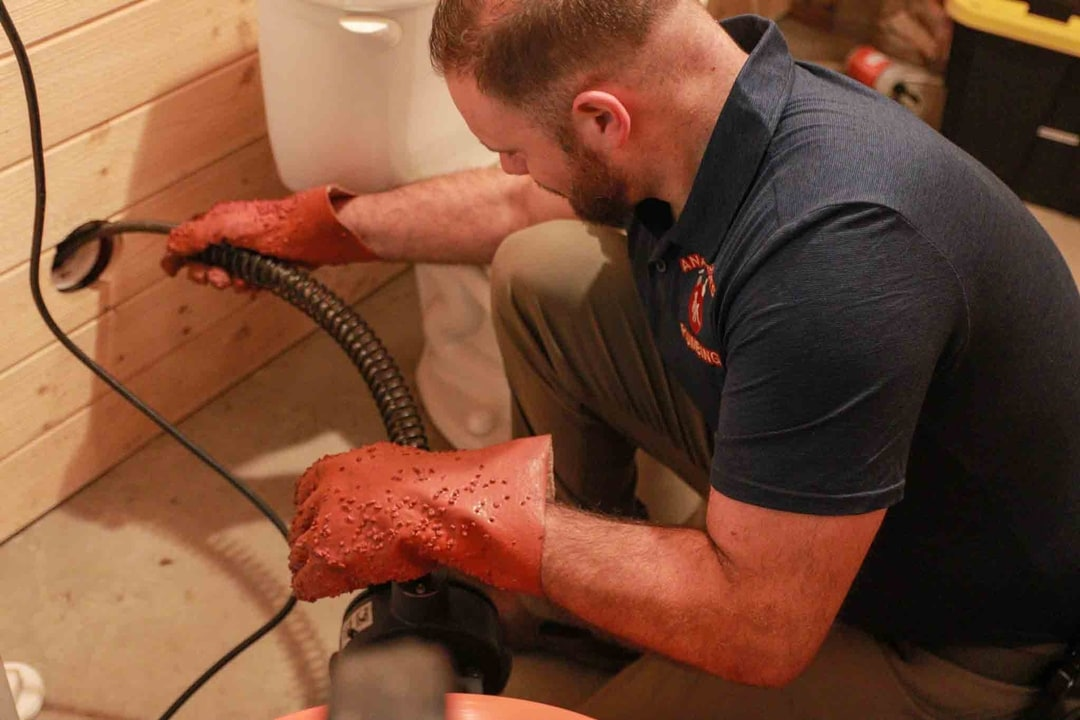 A plumber unclogging a clogged drain or performing leak detection.