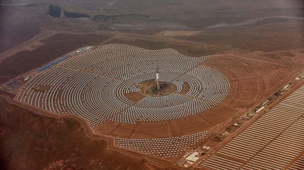 Unzählige circular angeordnete Spiegel in der Wüste Marokkos, die auf ein hohen Turm in der Mitte des Kreises gerichtet sind.