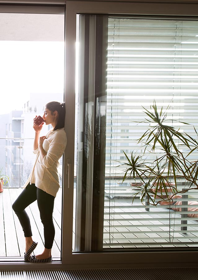 Woman drinking coffee next to Bifold blinds.