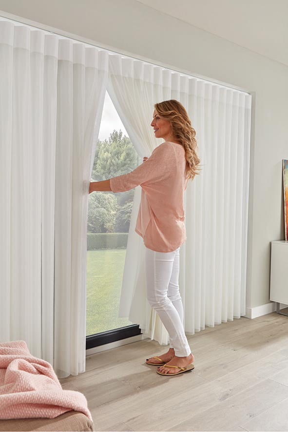 Woman pulling back curtains to look outside.