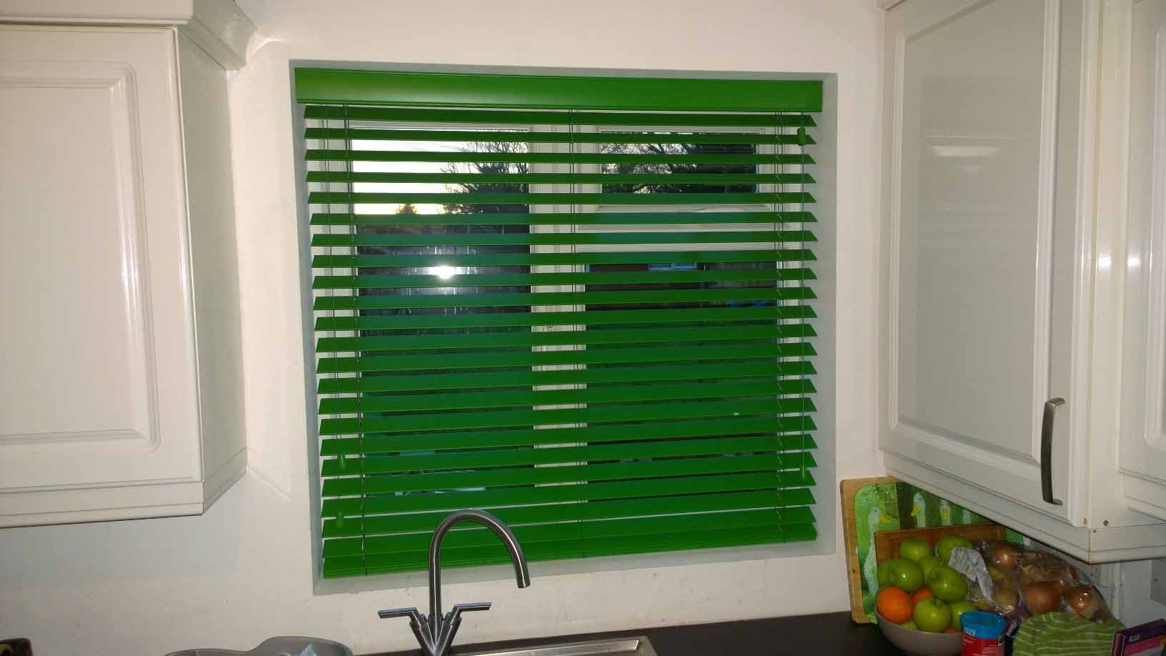 Green Venetian blinds.