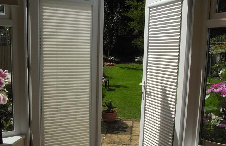 Door blinds on open door leading to garden.