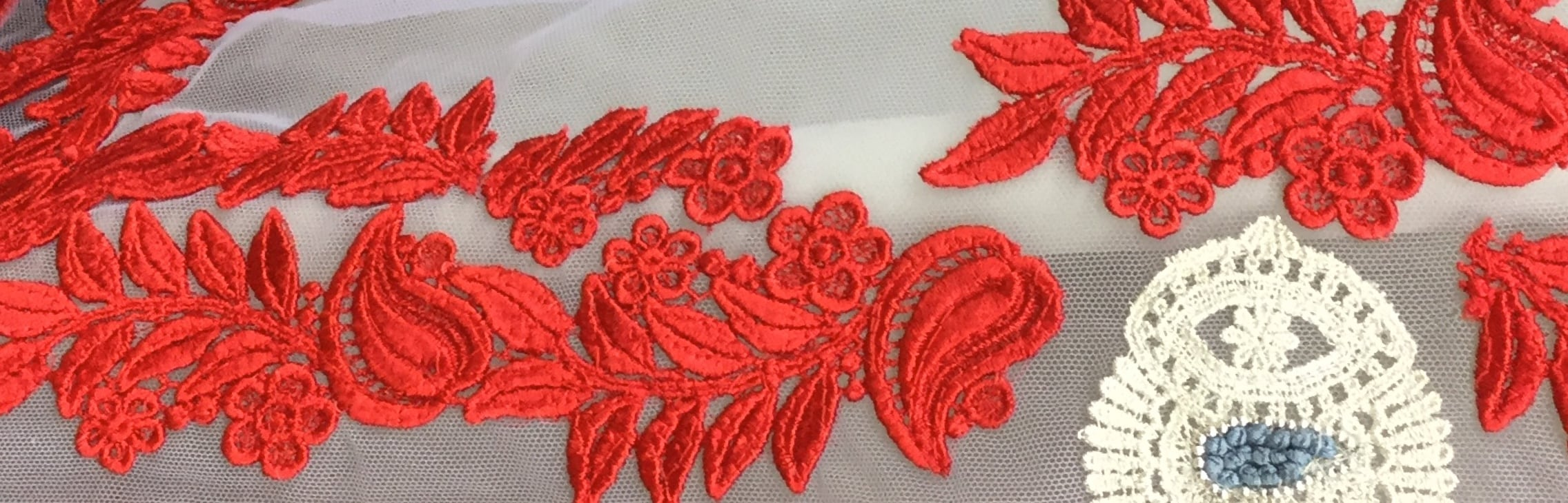 Harlequinade header image: white tule fabric with red embroidery