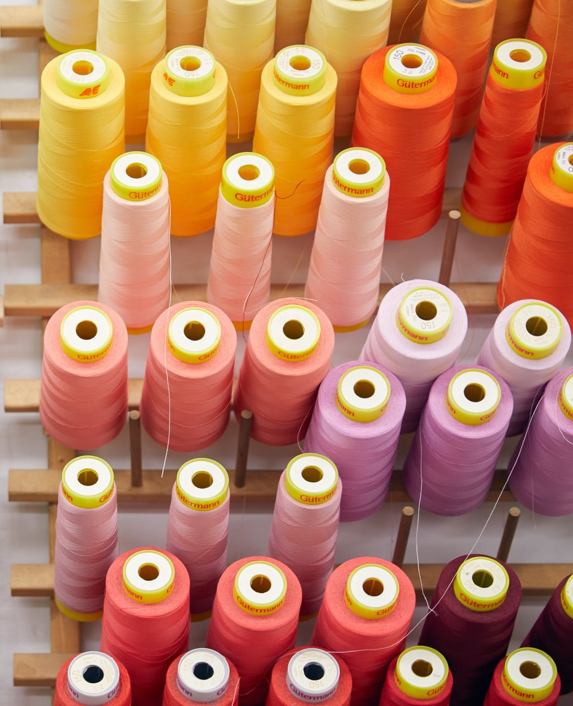 Pink, orange, and yellow spools of thread.
