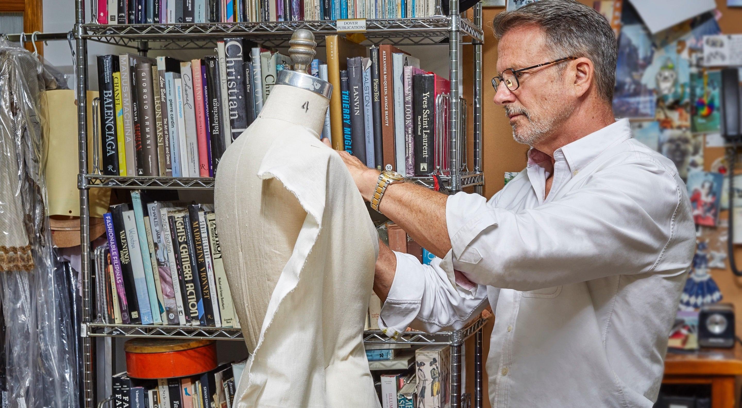 Eric Winterling adjusting fabric on a mannequin with bookshelf behind him.