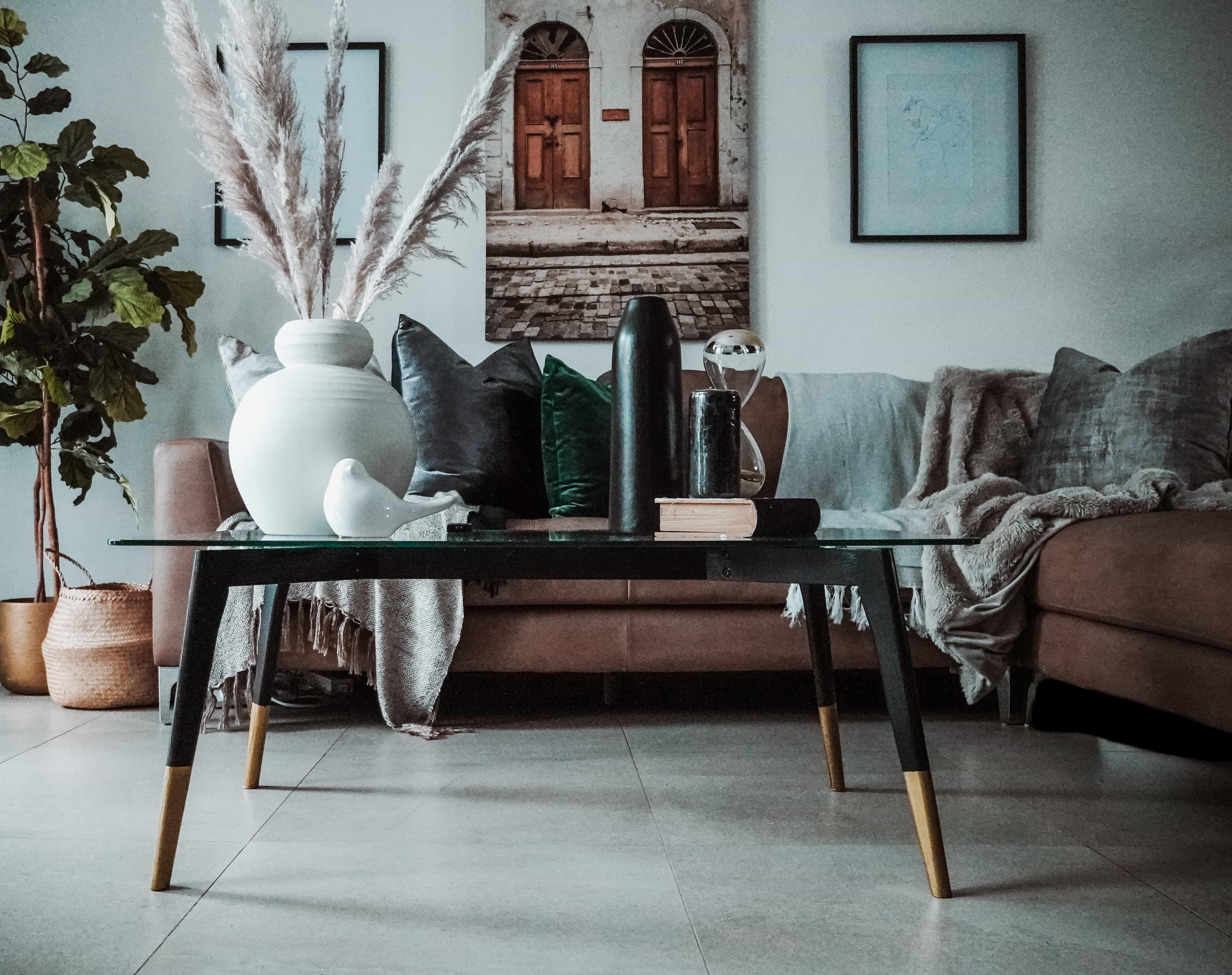 Ett vardagsrum med fin inredning och plädar.