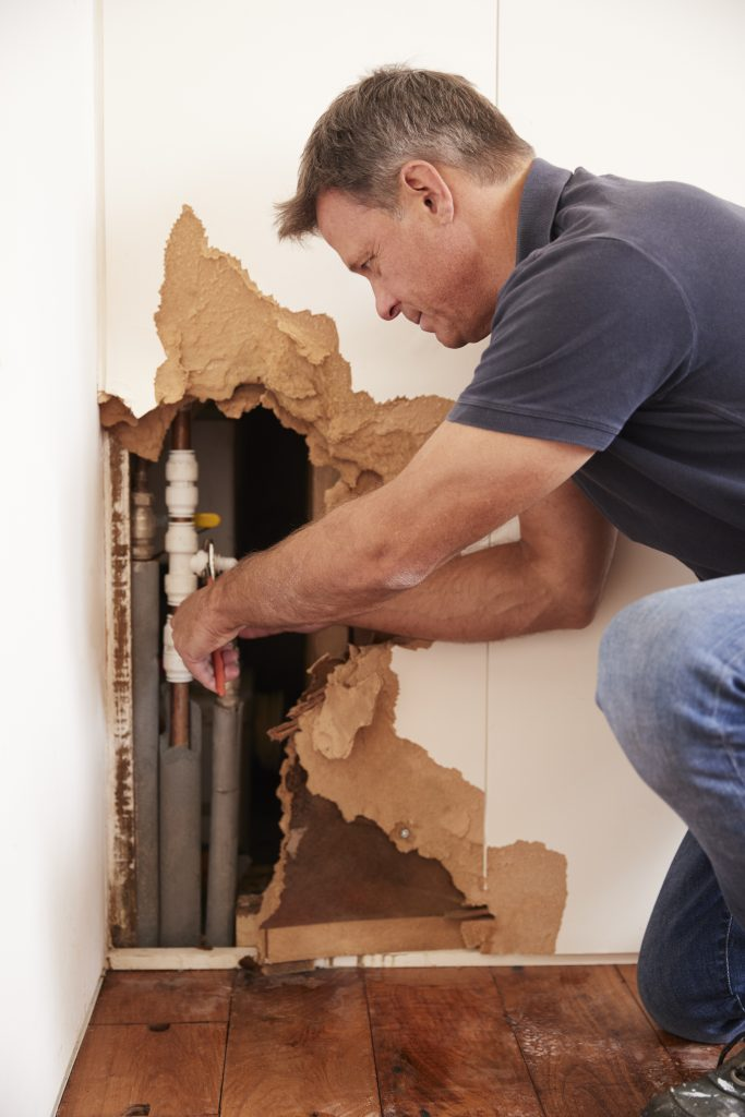 A plumber working on a pipe behind a wall