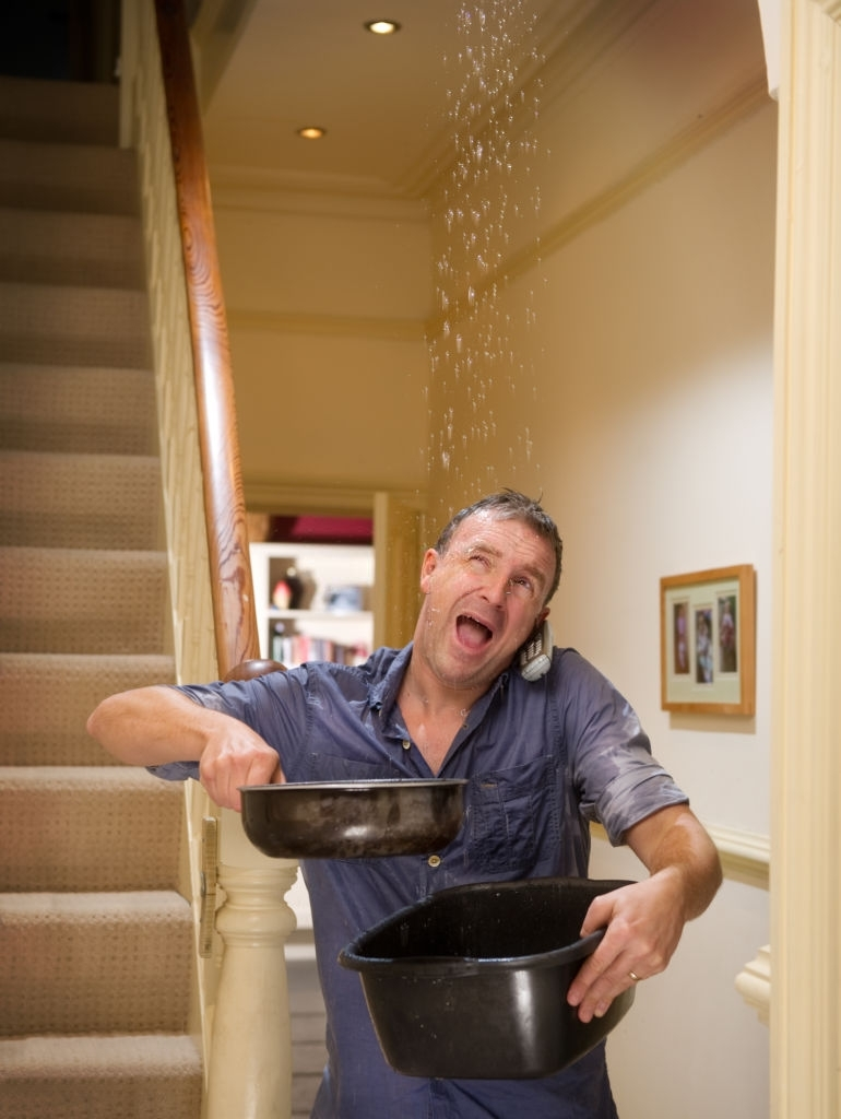 A distressed person calling a plumber whilst holding buckets trying to catch the water from a burst pipe