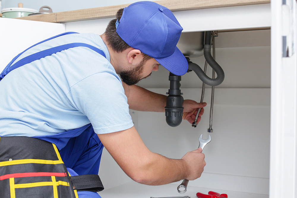 A plumber working on a sink