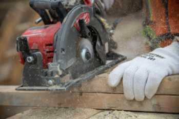 Worker sawing wood with circular saw