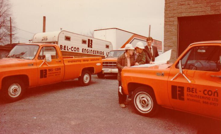 2 orange trucks pictured on job site in 1970s