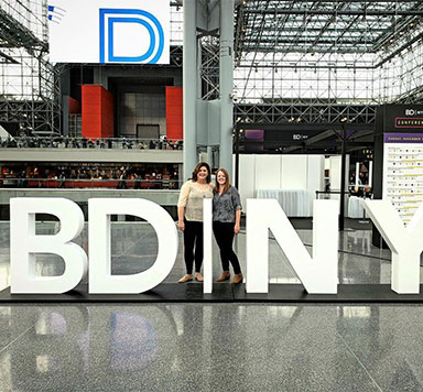 Two women in behind a BDNY sign