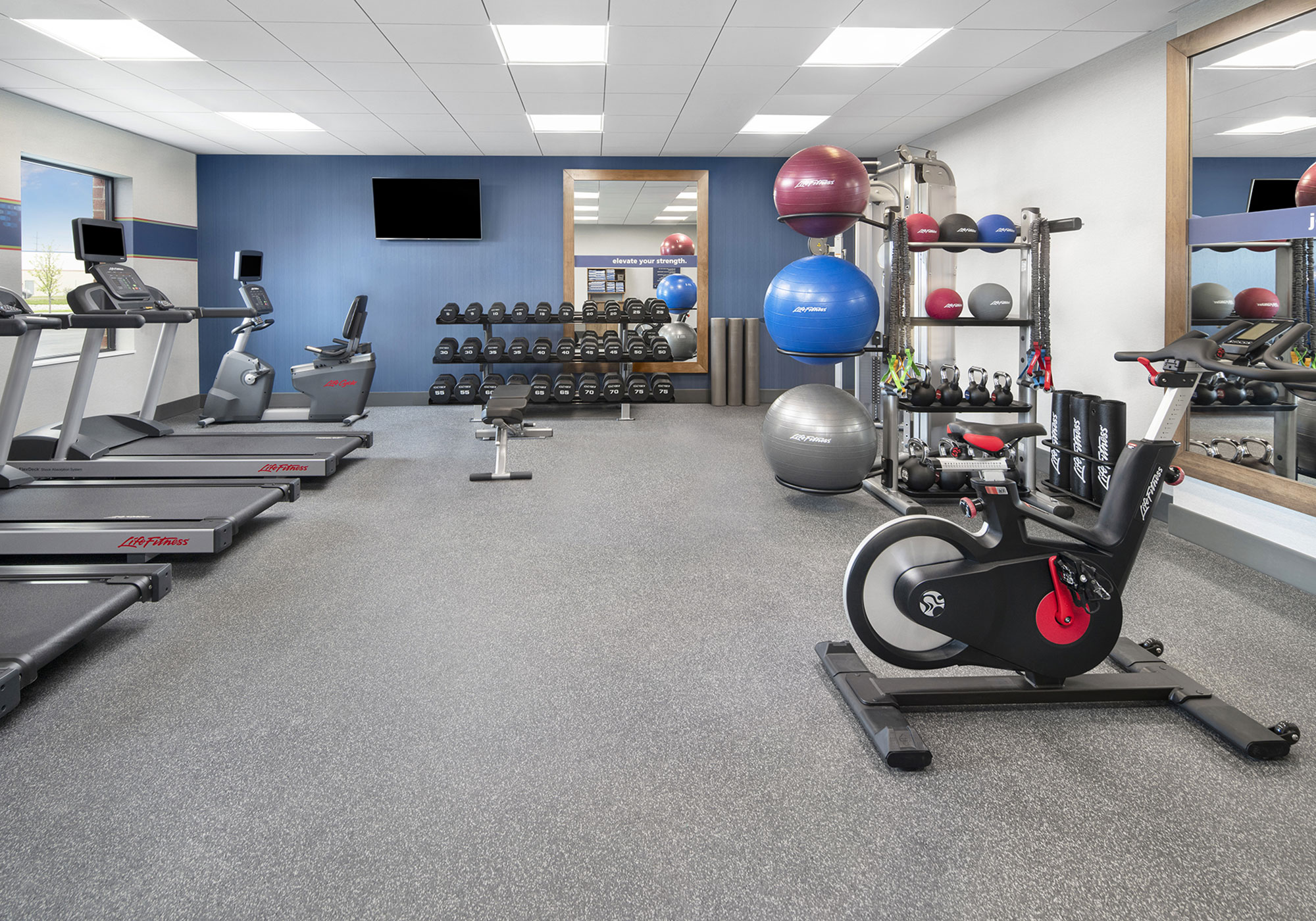 Workout room with exercise bike and tradmills