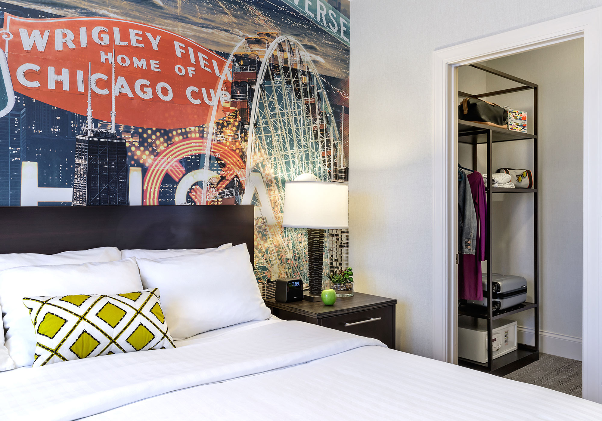 A bed with Wrigley Field art on the wall behind it