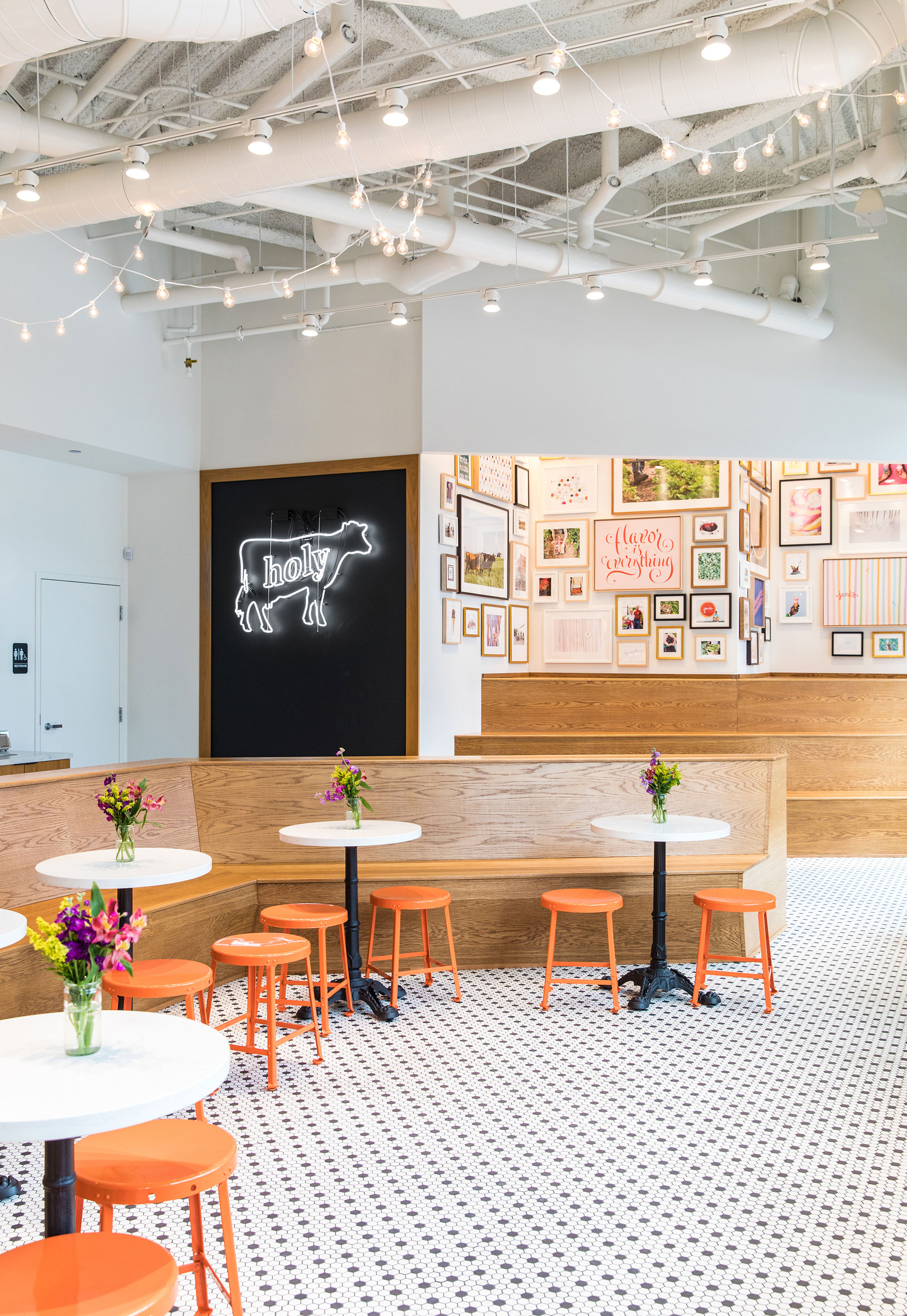 """Rustic dining room with a neon cow that has """"holy"""" on it"""