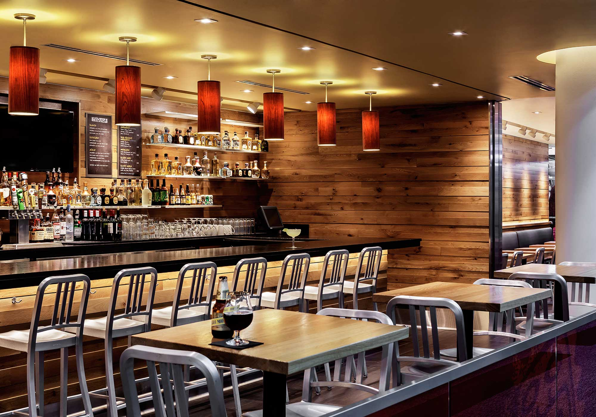Fancy bar with light wood tables and chairs