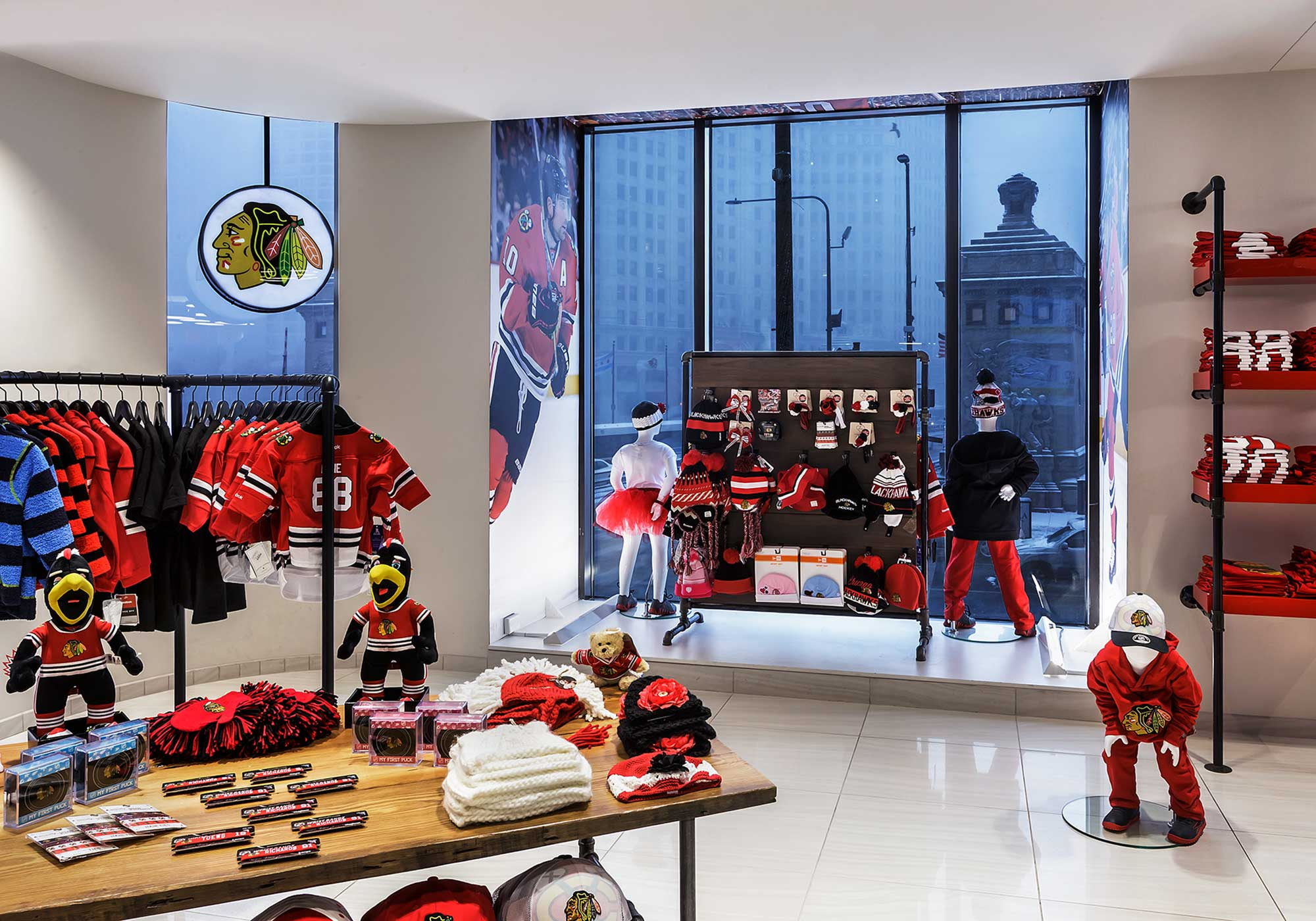 Display of children's clothing and stuffed animals with a window out onto the city in the background