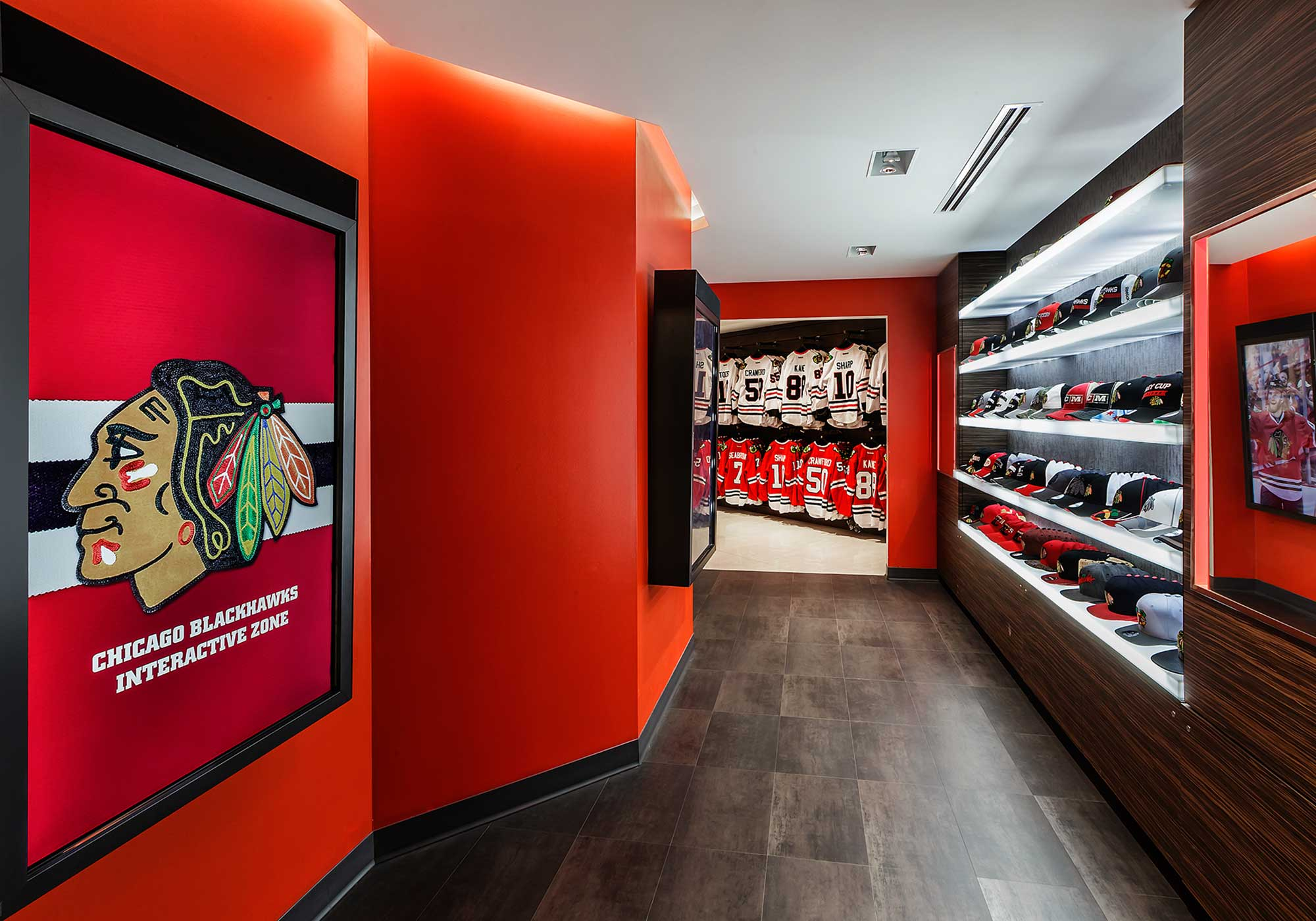 Display of baseball caps with Blackhawks logo and a framed picture of the logo mounted on the wall