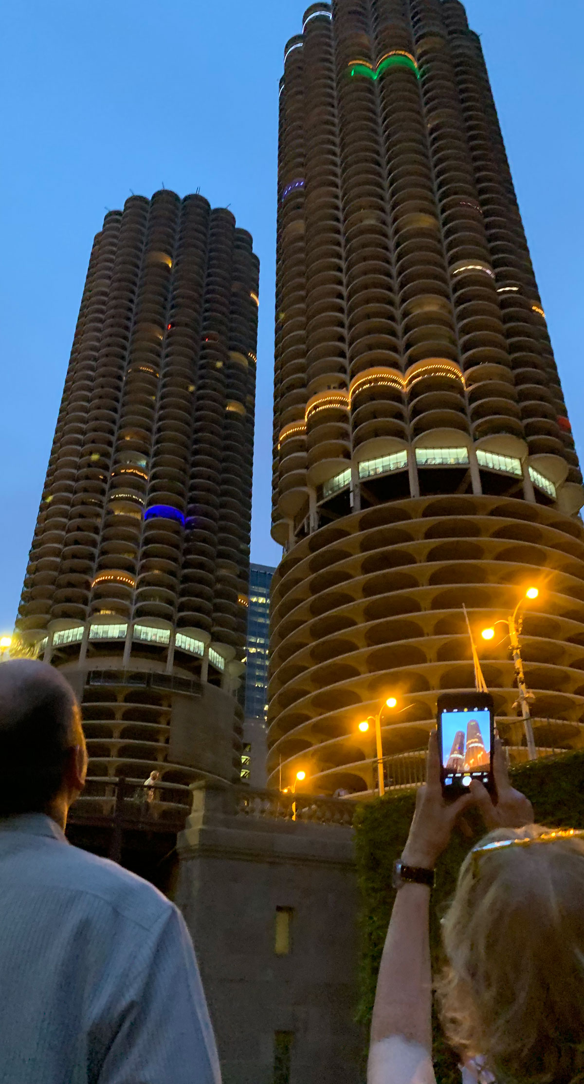 A man and woman look up at two skyscrapers