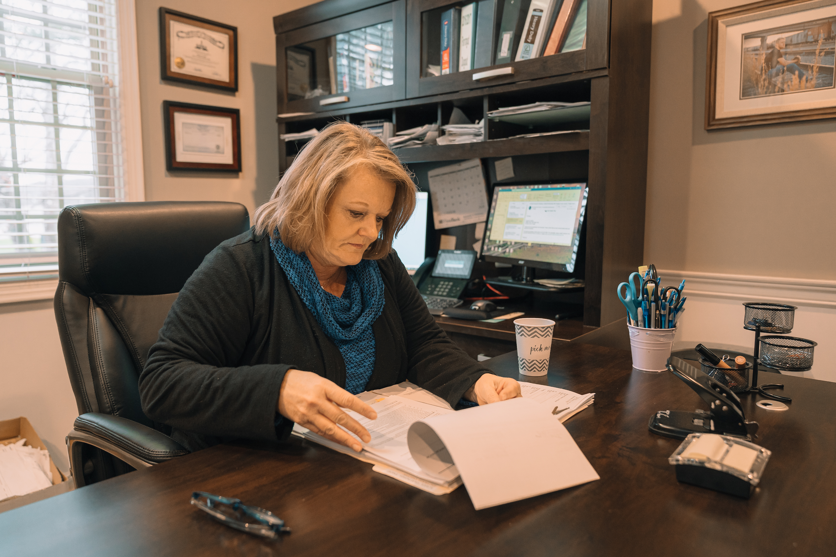 Teresa, Owner of Aspen Title and Escrow is working at her desk inside her office located in East Tennessee in the Knoxville area