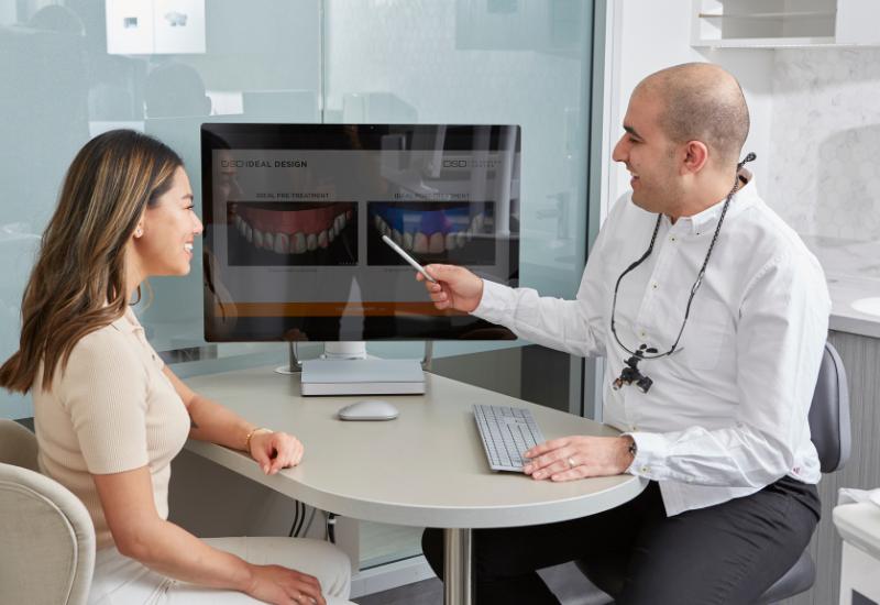 A smiling patient at delight dental mascot discussing Invisalign treatment