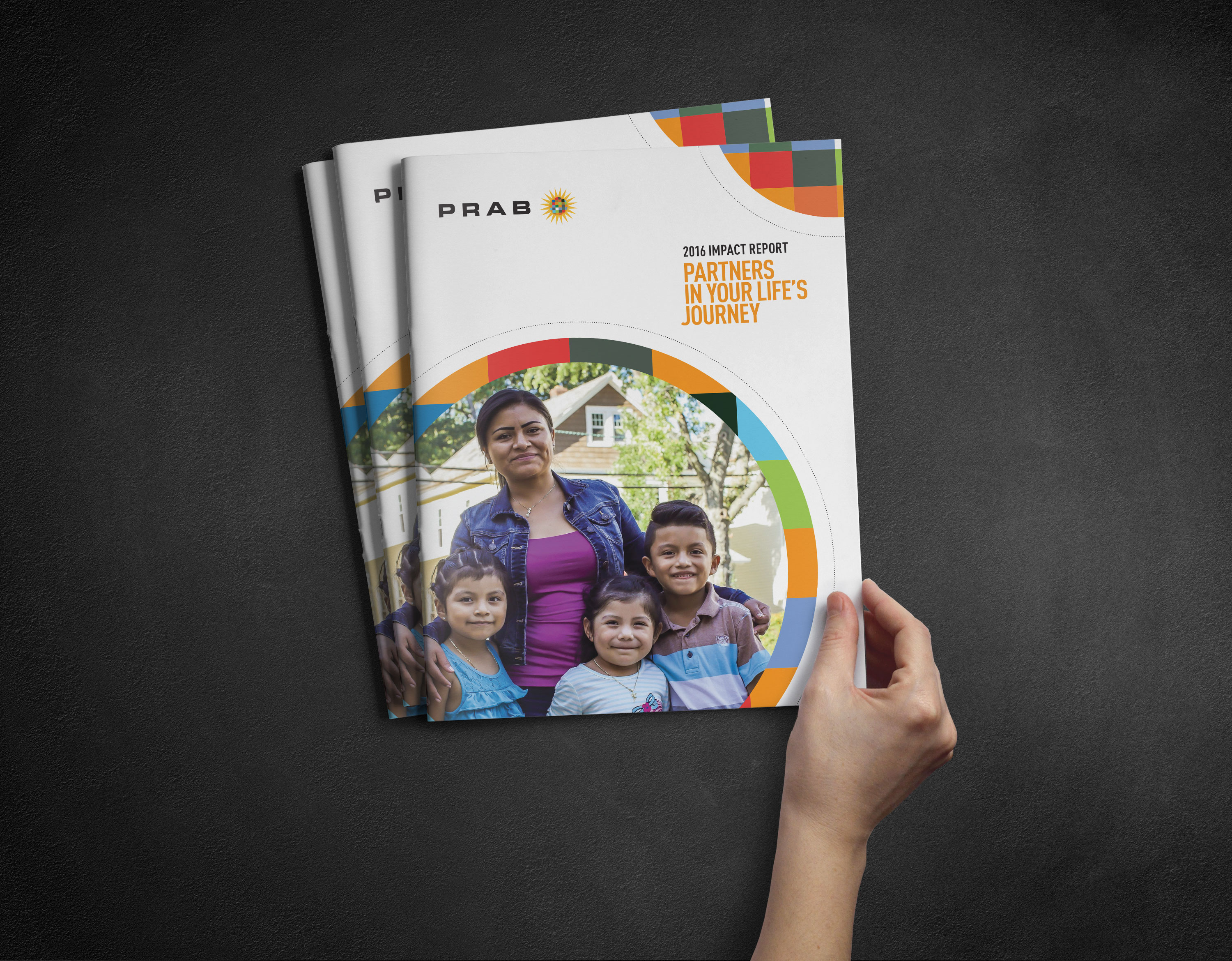 Hand holding PRAB Impact Report publications
