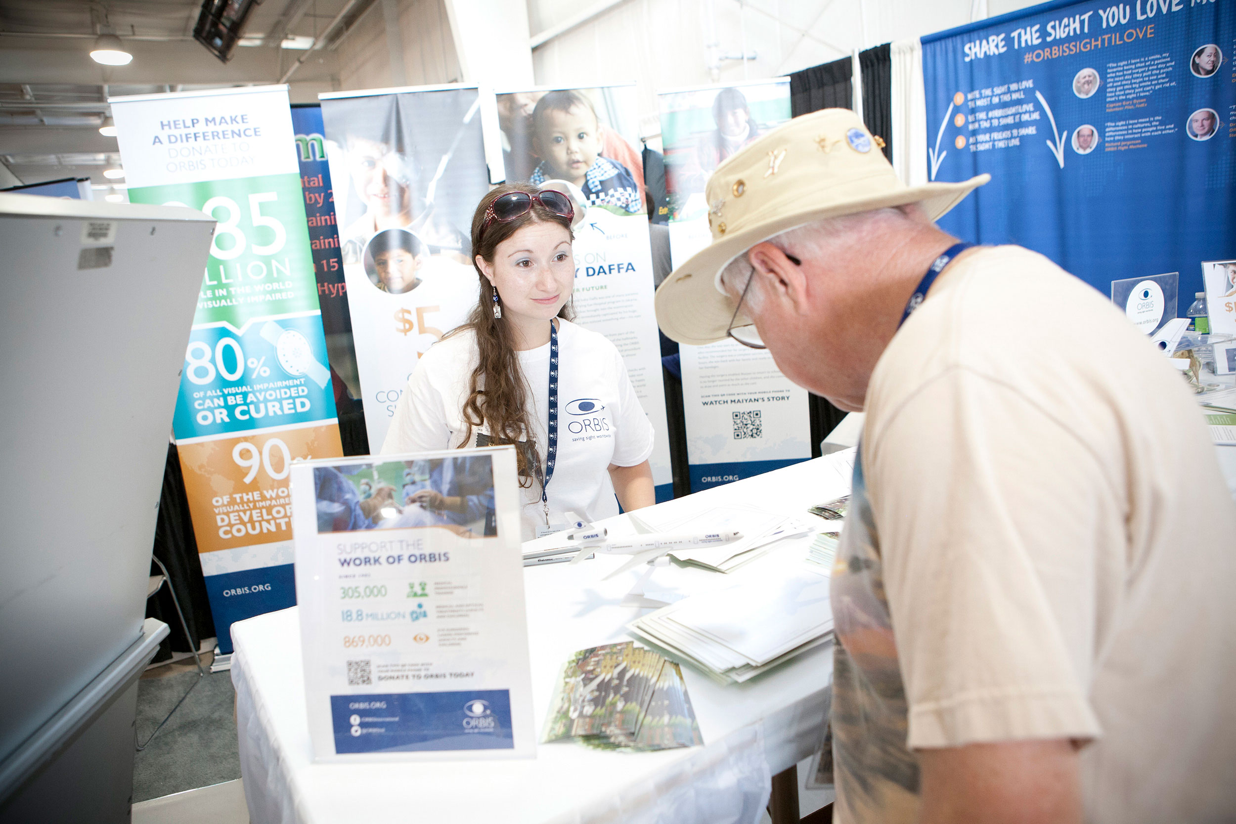 attendee interacting with Orbis staff member