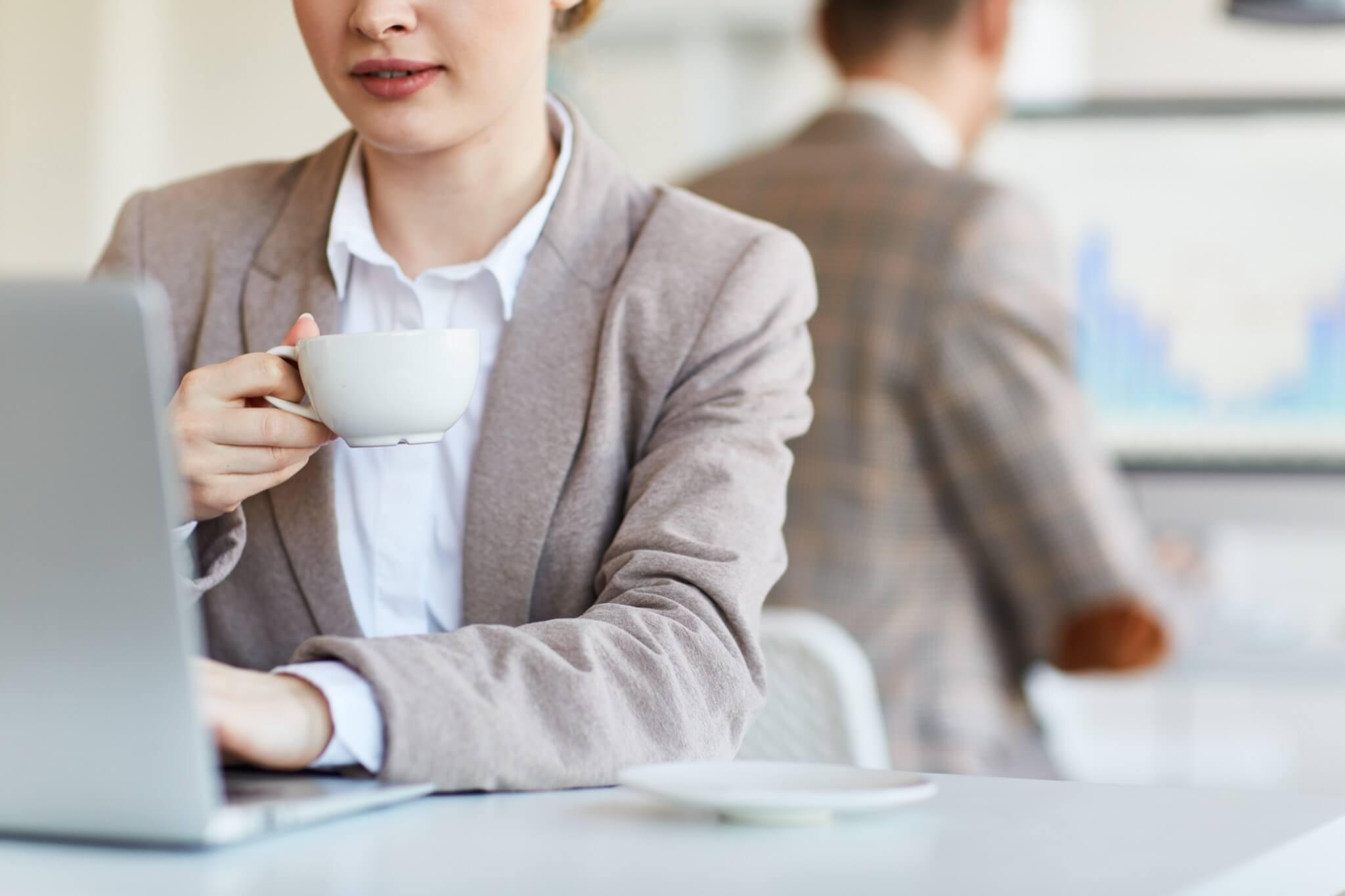 Drikker kaffe på jobben med kollegaer.