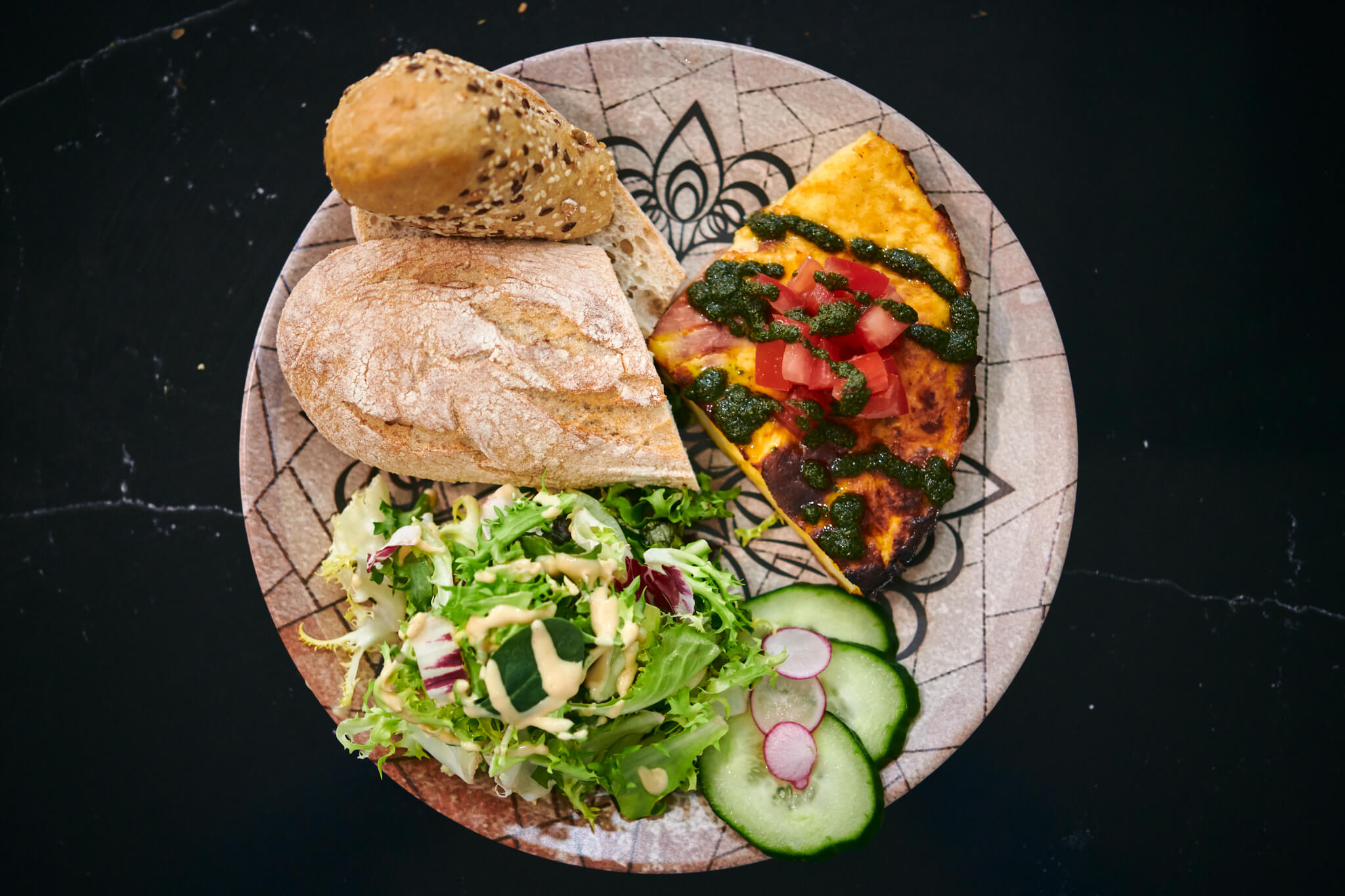 A plate with frittata bread and greens (shot from above)