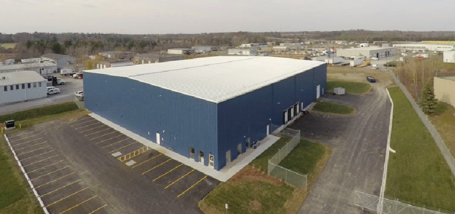 Aerial view of warehouse with parking lot surrounded by other industrial buildings
