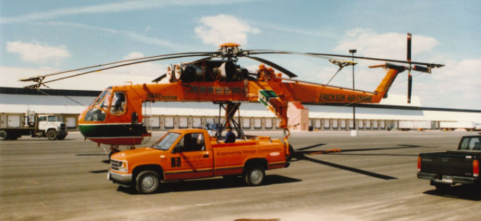 orange helicopter sitting behind an orange truck with warehouse in background