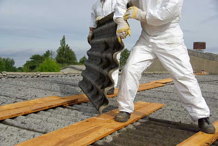 worker safely removing a panel of asbestos from roof while wearing hazardous materials protective equipment