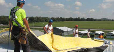 workers on a roof installing sheets of insulating material
