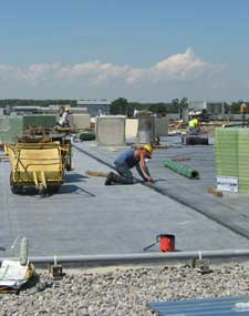Workers work on repairs to a commercial flat roof.