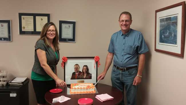business owners Tom Gunsinger and Michelle Stephens cutting cake