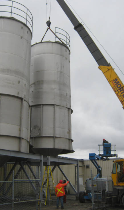 crane placing silo on building with supervisor pointing