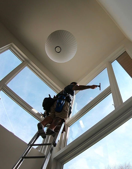 Interior residential high ceiling windows getting cleaned.