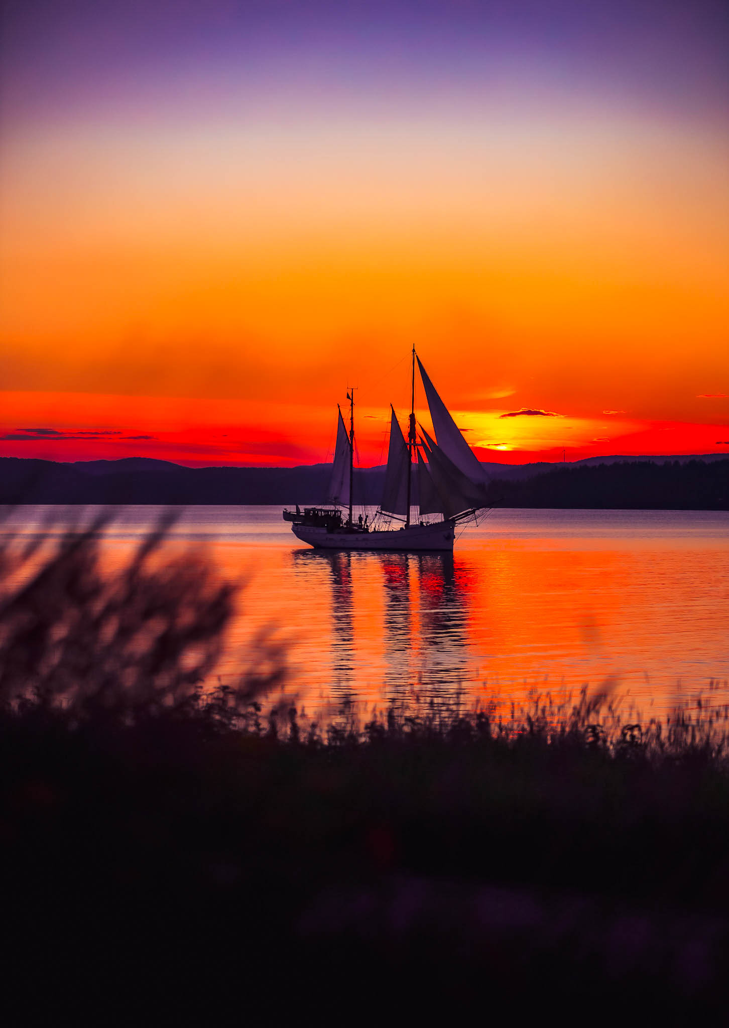 segelfartyg seglar mot solnedgång