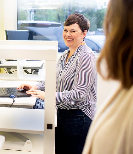 woman at computer smiling and looking at camera