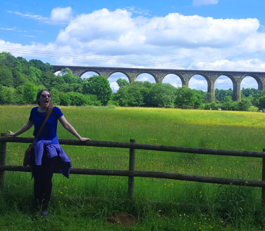 Lauren in the countryside with a bridge in the background