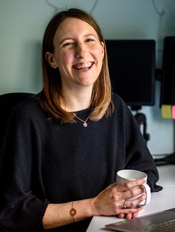 Lauren smiling holding a mug
