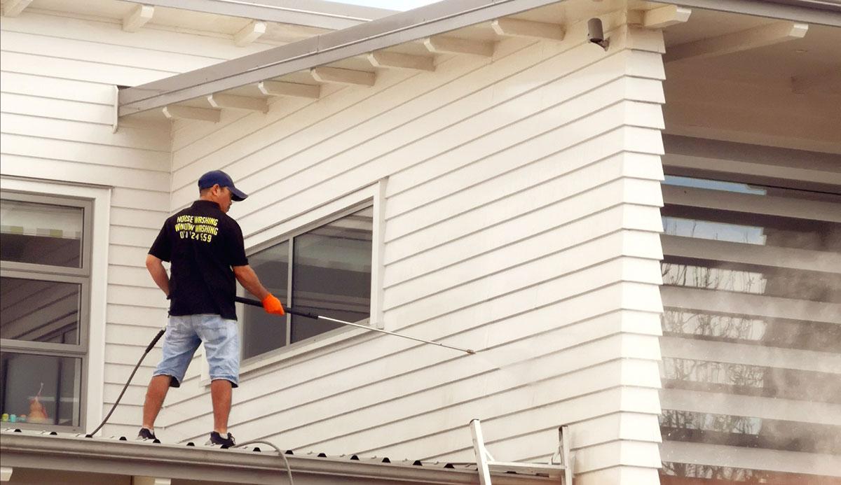 A man pressure washing an house siding.
