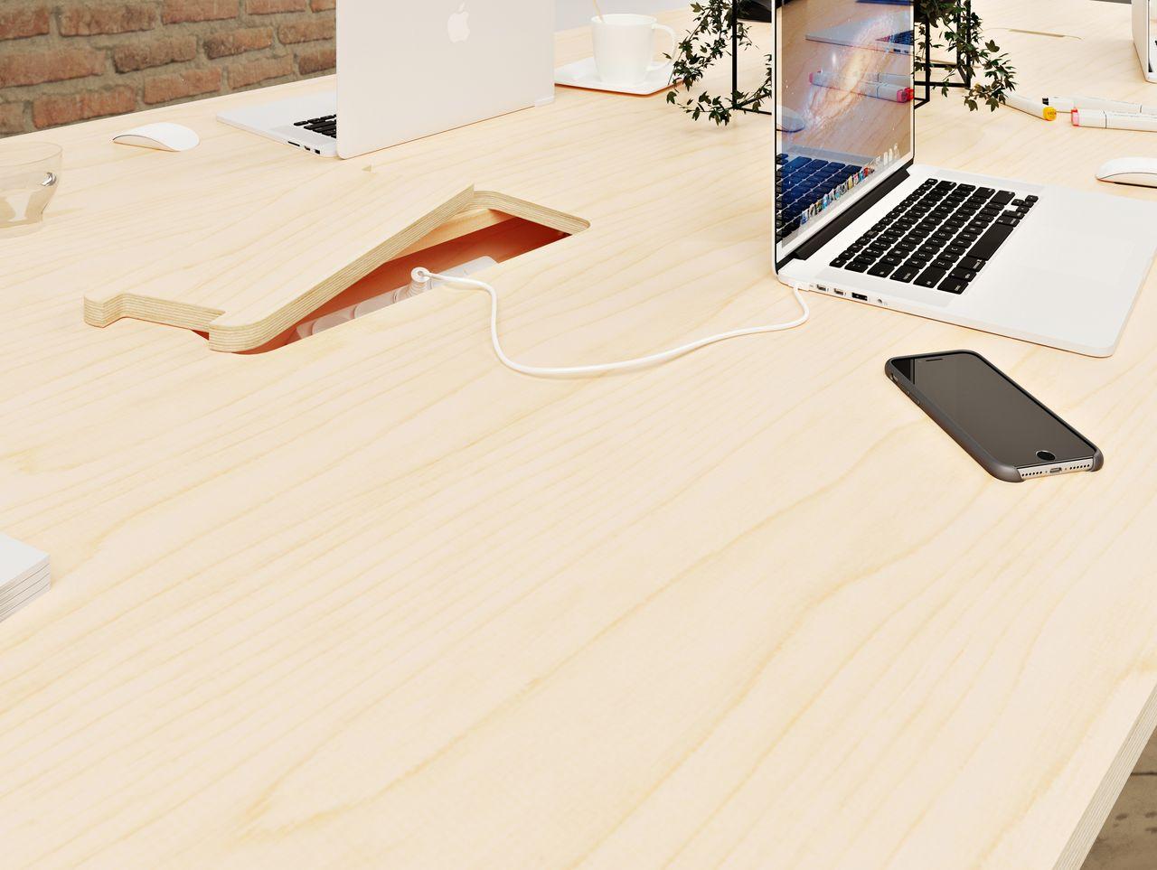 Table de réunion en bois avec des prises électriques intégrées au plateau et des ordinateurs branchés