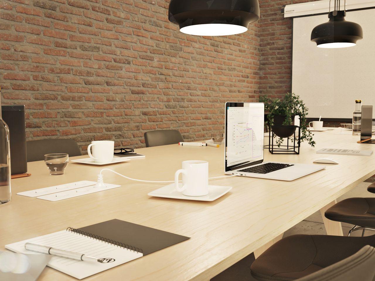Table de réunion avec prises électriques intégrées et ordinateurs branchés