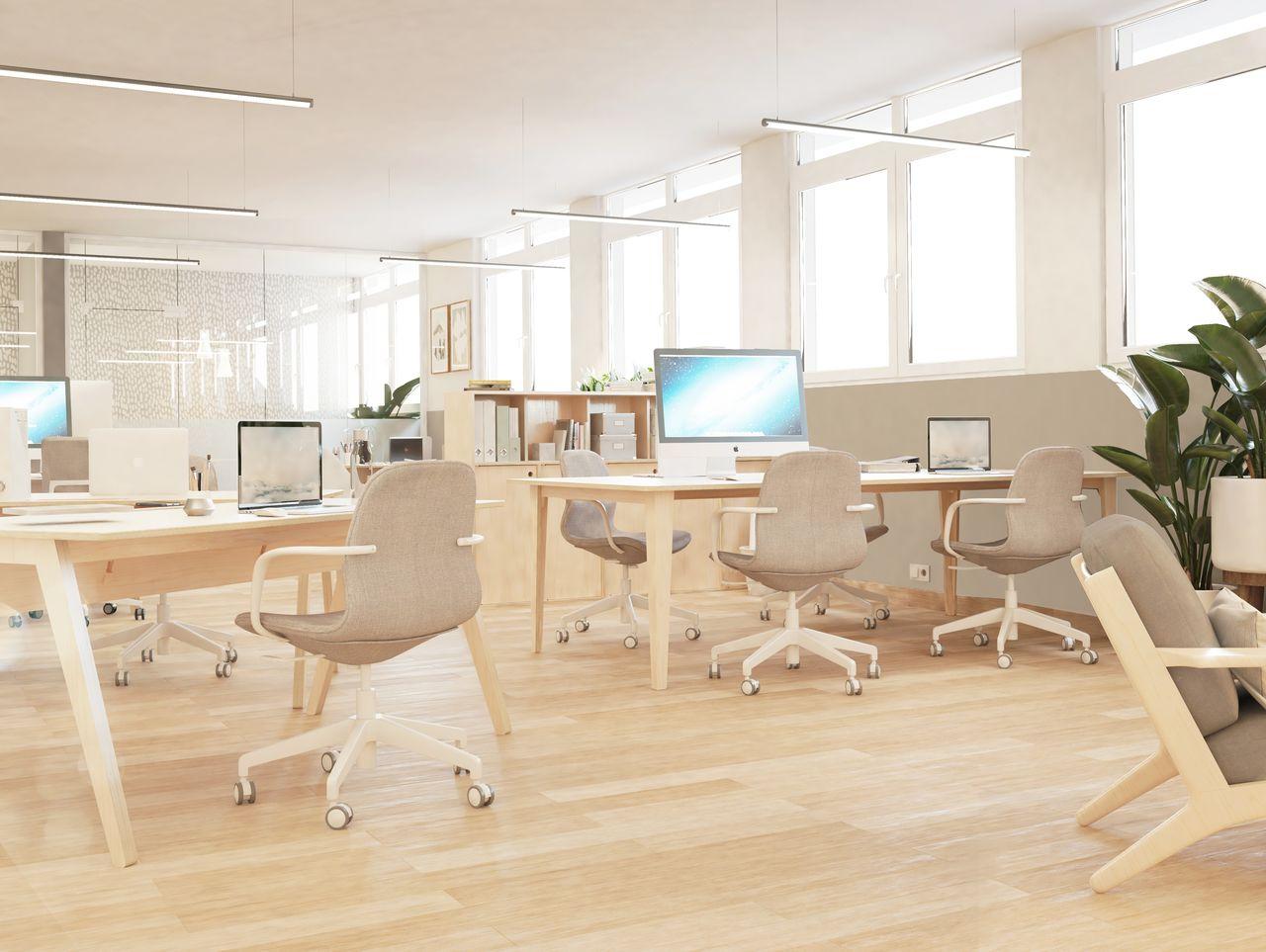 Ordinateurs sur bureaux en bois avec sièges gris dans un open space design d'entreprise