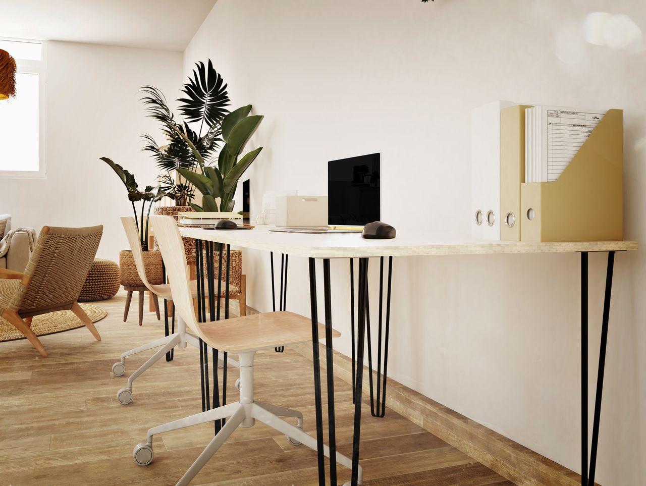 Bureau en bois et pieds en métal contre un mur avec un ordinateur, dans un espace de travail au style bohème avec des plantes et des meubles en osier