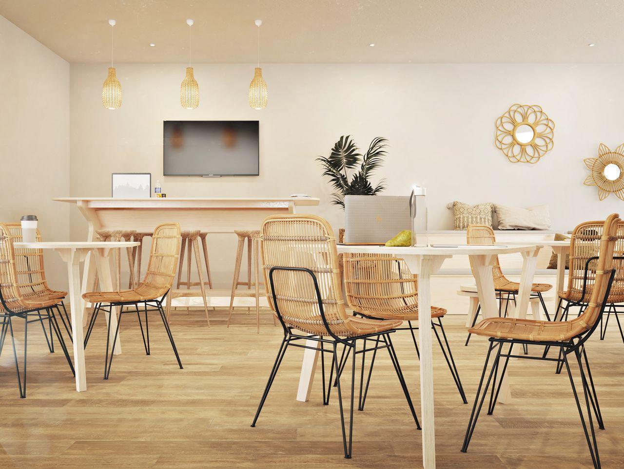 salle de réunion créative avec tables en bois, assises en osier et luminaires aux tons dorés pour une ambiance et un style bohème et végétal