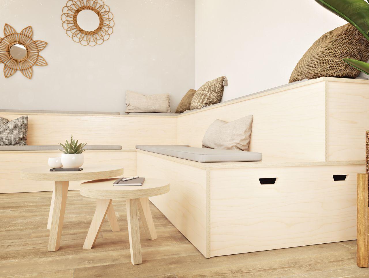 Estrade et table basse gigogne en bois dans un espace informel avec coussins sur les assises, miroirs en fleurs accrochée à un mur couleur taupe